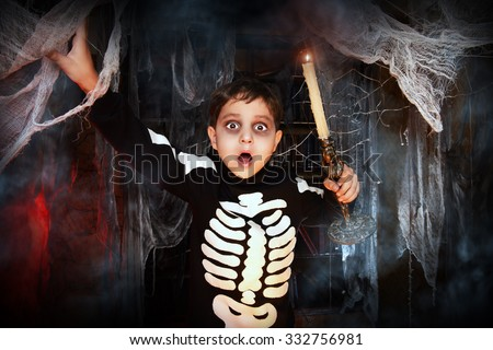 Scary funny boy in a costume of skeleton in a wizarding lair. Halloween party. Halloween decorations. - stock photo