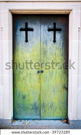 Scary green moss-covered iron crypt doors. Christian crucifixes at the top of each door. - stock photo