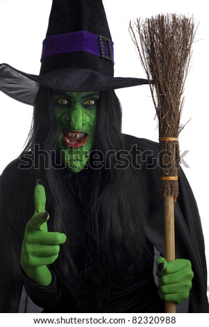 Scary green witch carrying her broom and pointing her finger, white background. - stock photo