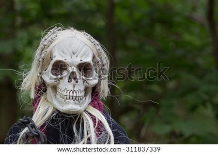 Scary grim reaper halloween prop in the woods - stock photo