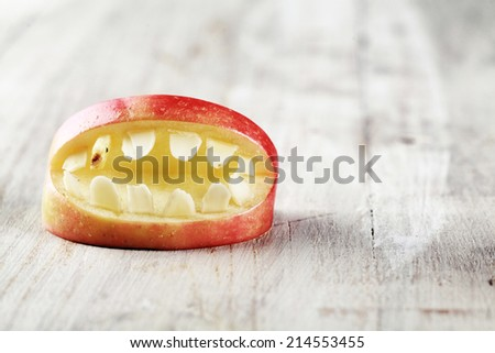 Scary Halloween apple mouth with bared teeth on a textured white background with copyspace for your greeting or invitation - stock photo