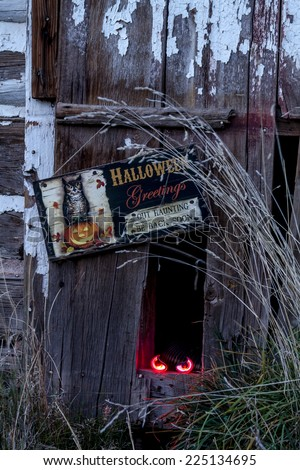 Scary Halloween glowing eyes in hole in old abandoned wood building with Halloween greetings sign - stock photo
