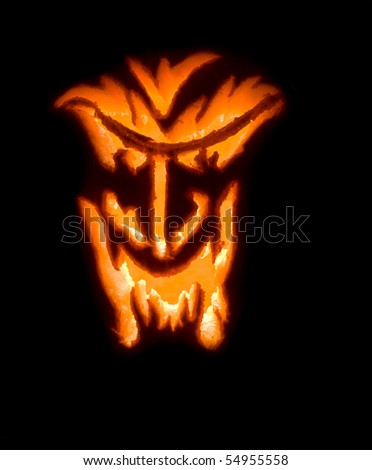 Scary Halloween jack-o-lantern with a horrifying face carved - stock photo