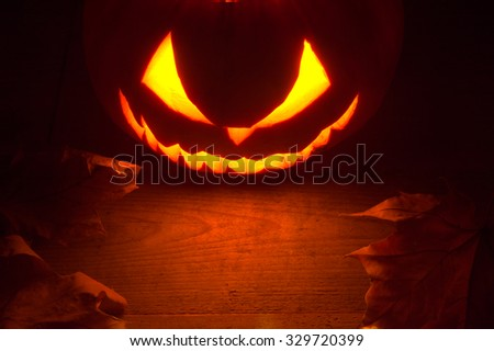 Scary halloween night with spooky evil face of jack o lantern at the top with red shadows on the wooden surface - stock photo