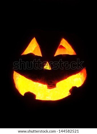 Scary Halloween pumpkin face glowing inside at black background - stock photo
