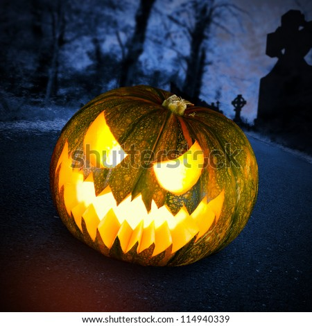 Scary halloween pumpkin in the dark forest at night - stock photo