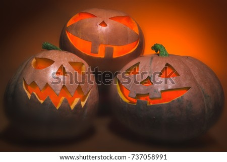 Scary Halloween pumpkins. Halloween card concept. Spooky glowing faces. Photo of three pumpkins of Halloween on a wooden table