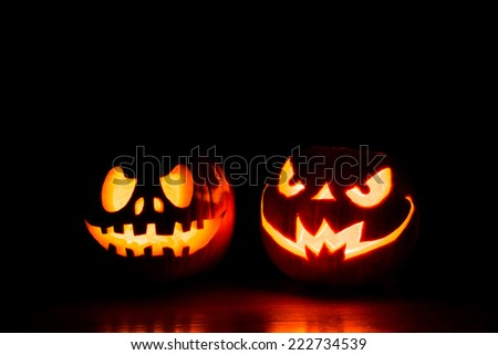 Scary Halloween pumpkins on a black background. Scary glowing faces trick or treat - stock photo