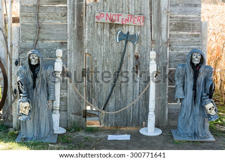 Scary Halloween Skeleton with Skull in Hand with Do Not Enter Door - stock photo