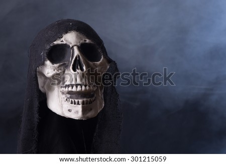 Scary Halloween skull prop on a smoky background - stock photo