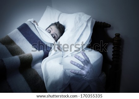 Scary hand coming out from under the bed - stock photo