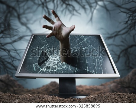 Scary hand sticks from computer - stock photo