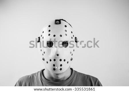 Scary hockey white mask on young man isolated on white background. Close up portrait.  - stock photo
