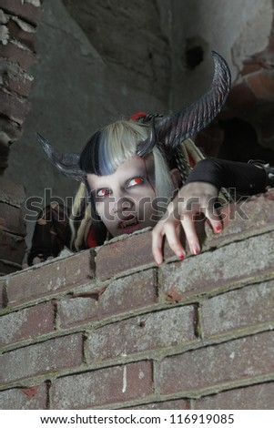 Scary hungry female demon crawling over old dirty brick wall. - stock photo