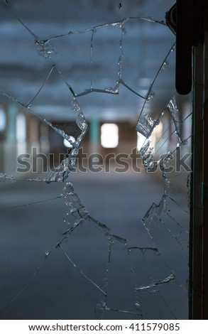 Scary image of broken glass in shards leading into an empty room in old hospital - stock photo