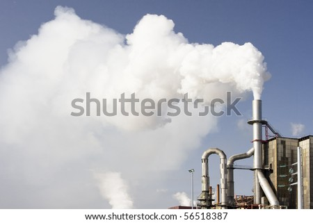 Scary image of white smoke coming out of industrial chimney (ecology problems)