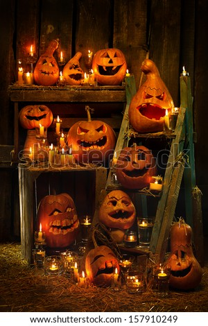 Scary Jack O Lantern Halloween pumpkins against wooden wall in darkness - stock photo