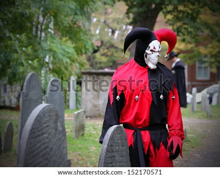 Scary Joker with skeleton face looking at the headstone on the graveyard - stock photo
