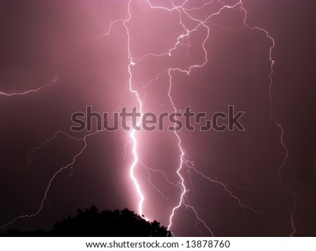 Scary lightning storm on a stormy night with tree getting struck - stock photo