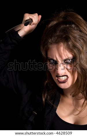 Scary looking woman about to stab something or someone - stock photo