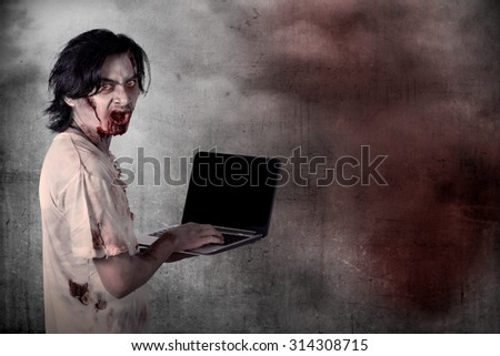 Scary male zombie typing with laptop over grunge background