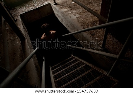 Scary man silhouette in the dark staircase with light only on the shoulders - stock photo