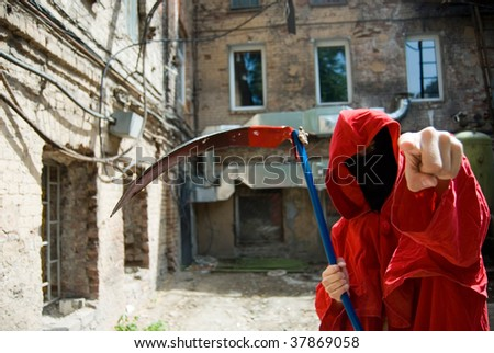 Scary masked person with a scythe points finger at his victim