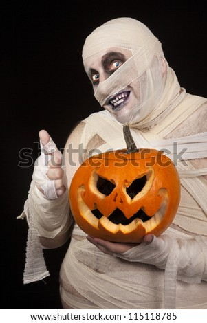 Scary  Mummy with Halloween pumpkin holding thumbs up. Funny smiling young man in mummy costume with holyday pumpkin