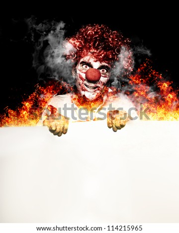 Scary Portrait Of A Creepy Circus Clown Holding A Blank Copyspace Board While Standing In Flames Of Fire In A Hot Halloween Specials Concept - stock photo