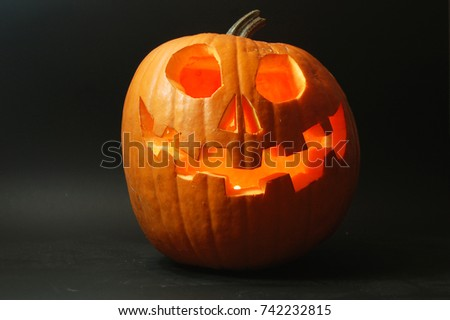 Scary Smiling Halloween Pumpkin which is lit up.