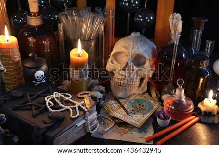 Scary still life with tarot cards, skull, old book, vintage bottles and candles on witch table. Halloween or esoteric concept. Black magic and occult objects in evil interior