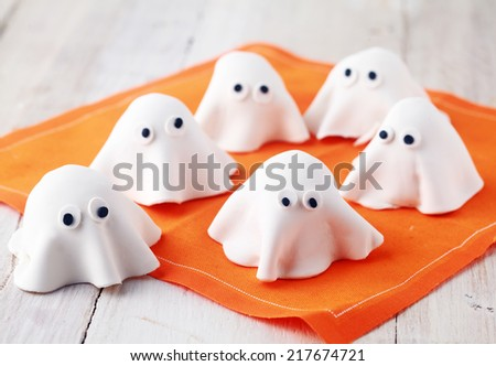 Scary white edible Halloween ghost appetizers for party snacks or treats for young children trick-or-treating on Allhallows Eve standing ready on a colorful orange napkin - stock photo