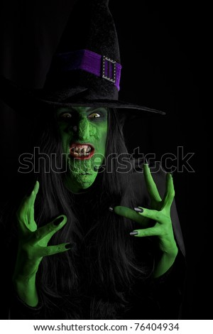 Scary witch about to attack. Low key lighting. - stock photo