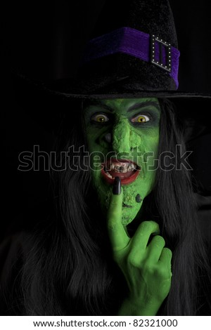 Scary witch, contemplating evil thoughts.  Low key lighting. - stock photo