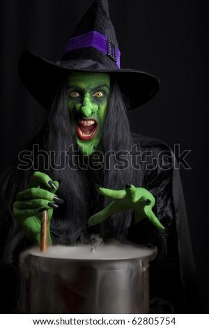 Scary witch stirring her cauldron. Low key lighting. - stock photo
