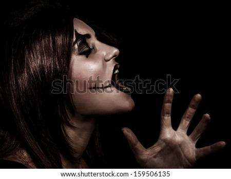 Scary witch yelling, side view of aggresive woman with painted face on black background, terrible grimace, Halloween party concept - stock photo