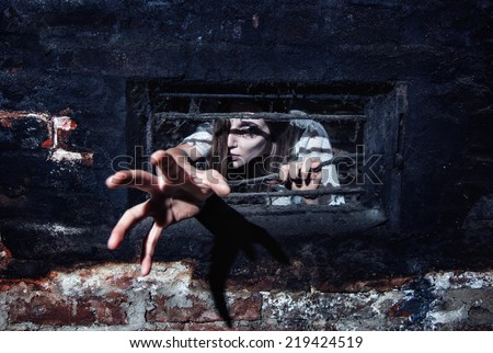 Scary Woman Attacking Through A Small Window With Bars In A Dark Hallway.