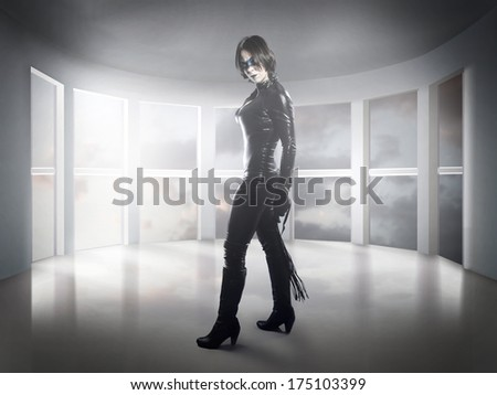 Scary.woman dressed in latex, whip and black wings - stock photo