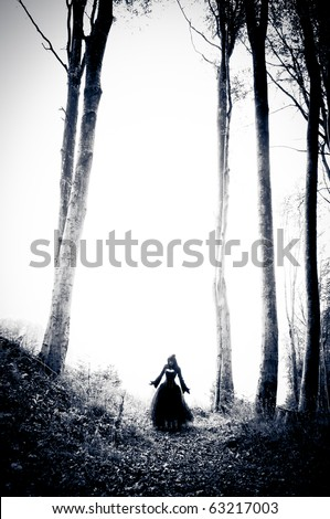 Scary woman from nightmares in black dress with trees around her - stock photo