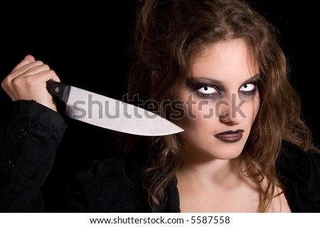 Scary woman holding out a knife as if ready to stab someone - stock photo