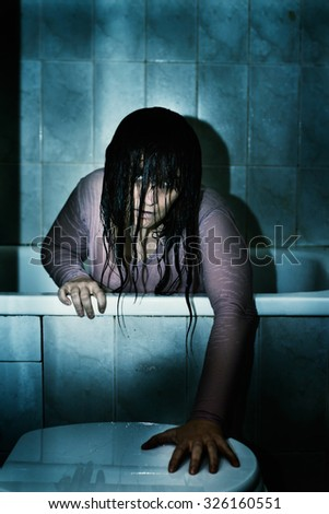 Scary woman in a bath coming out of the water all wet, Halloween and horror theme - stock photo