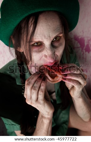 Scary zombie scout munching on a tasty human ear - stock photo