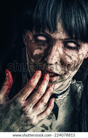 Scary zombie woman  with white eyes and bloody hand - stock photo