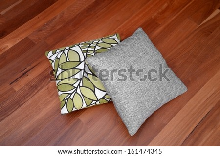 Scatter cushions isolated on a wooden floor
