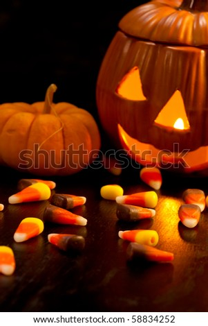 Scatter Halloween candies and orange pumpkin with light - stock photo