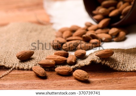 scattered brown almonds on a wooden table, close-up - stock photo