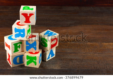 scattered children's wooden blocks with colorful letters on wooden table - stock photo