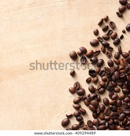 Scattered coffee beans on textured brown table. Top view, copy space - stock photo