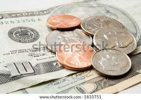 Scattered coins atop a ten dollar US bill. - stock photo