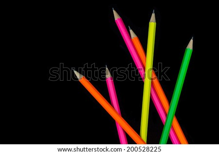 scattered colored pencils on black - stock photo